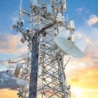 Une tour de transmission 5G devant un coucher de soleil.
