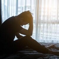 Un homme dans son lit se tient la tête