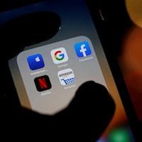 Une main tient un téléphone cellulaire où sont affichées les icônes des applications des géants.
