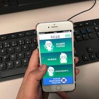 Une main tient un téléphone intelligent sur lequel est ouverte une application mobile.