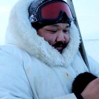 Un homme portant un manteau d'hiver, une tuque et des lunettes de ski regarde son téléphone cellulaire.