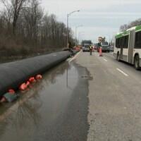 Un long boyau rempli d'eau longe le bord de l'autoroute.