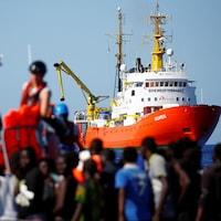 Des migrants sur une embarcation en pleine mer.