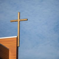 Une croix accrochée à la structure d'un bâtiment.