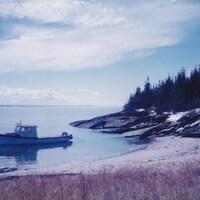 Le rivage et le bateau de traverse à l'Île aux Basques, au large de Trois-Pistoles.