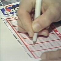 Main remplissant au stylo les numéros d'un billet de Lotto 6/49