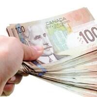 Une main tenant une liasse de  billets de 100 $