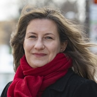 Ariane Mignolet porte un manteau noir et un foulard rouge autour de son cou.