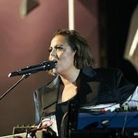 La chanteuse est sur la scène devant un micro.