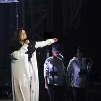Une femme chante lors d'un concert.