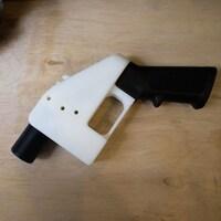 Une petite arme à feu est posée sur une table en bois. Son canon est très court.