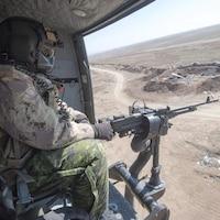 Un mitrailleur installé à bord d'un hélicoptère canadien.