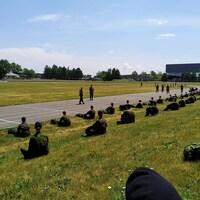Des recrues assises au sol à deux mètres de distance les unes des autres.