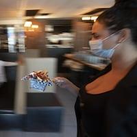 Une jeune serveuse portant un couvre-visage transporte un petit panier de pommes de terre frites qu'elle tient avec un bâtonnet.