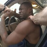 George Floyd, assis dans sa voiture, est tiré par les bras de policiers.