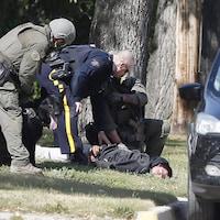 Un policier est menotté et tenu à terre par trois agents de police, l'un d'entre eux tient un chien sur une laisse.