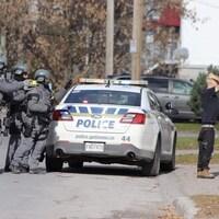 Un groupe de policiers et un suspect, les mains sur la tête.