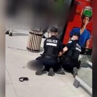 Deux policiers agenouillés, dont un pose son genou sur le cou de la personne arrêtée, près d'un abribus.