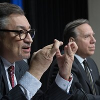 Les deux hommes en conférence de presse. Le Dr Arruda se croise les doigts.