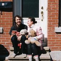 Un couple souriant est assis sur des marches devant leur maison.