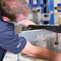 Un homme assemble des composantes mécaniques.