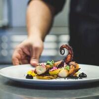 Un chef met la touche finale à un plat du restaurant Le poivre noir