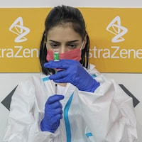 Une infirmière remplit une seringue de vaccin.