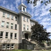 Une ancienne école avec un clocher.