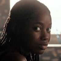 Une adolescente regarde vers la caméra.