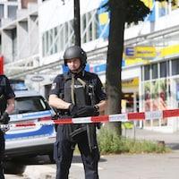 Des policiers montent la garde devant le supermarché de Hambourg où a eu lieu l'attaque.