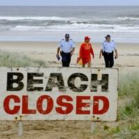 Des policiers discutent avec un sauveteur sur une plage fermée d'Australie .