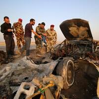 Les forces irakiennes font l'inspection d'une voiture brûlée, où a eu lieu un attentat à la bombe sur une autoroute près de la ville de Nassiriya, au sud de l'Irak.