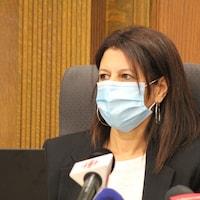 Géhane Kamel au micro avec un masque.