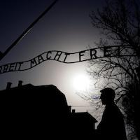 Un homme se tient sous un portail de fer forgé arborant le slogan nazi « Arbeit macht frei » à l'ancien camp de concentration d'Auschwitz.