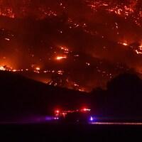 Un camion des pompiers passe devant un flanc de montagne en proie aux flammes dans la nuit.
