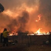 Un pompier observe des flammes.