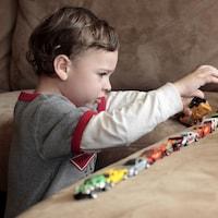 Un enfant autiste joue avec ses jouets