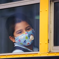 Un élève portant un masque dans un autobus scolaire.