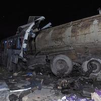 Un camion-citerne et un autobus défoncé entourés de débris.