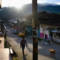 Trois personnes et un chien marchent dans la rue d'un village en Colombie.