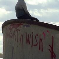 Un jeune est assis sur une structure en ciment.