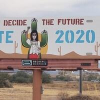 Une pancarte dans une communauté autochtone représente une femme autochtone portant un bulletin de vote pour les élections de 2020 et l'inscription ''vous décidez du futur''.