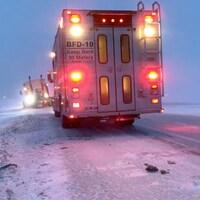 Un camion de pompiers sur la route vient en aide à un semi-remorque qui a effectué une sortie de route.