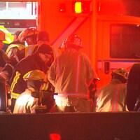 Des pompiers et des ambulanciers s'affairent devant une ambulance.