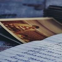 Sur la photographie, on peut voir des lettres écrites à la main et une vieille photographie d'une femme avec son enfant.