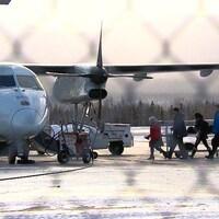 Passagers qui embarquent dans un avion à l'aéroport de Gaspé.