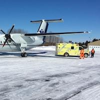 Un avion-ambulance et une ambulance sur la piste de l'aéroport de Matane en hiver.