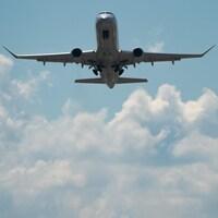 Un avion, dont on voit surtout le dessous, est vu dans le ciel, lors d'une journée ensoleillée.