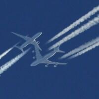 Deux avions commerciaux se croisent dans un ciel bleu.