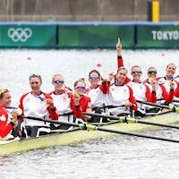 Les huit rameuses arborent fièrement leur médailles dans leur bateau.